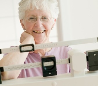 Senior woman weighing self on scale